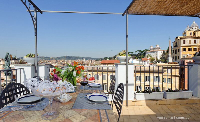 "Table to dine ""al fresco"" in the Rome Spanish Steps Seagulls penthouse: view towards the Spanish Steps, the Borghese Gardens and Villa Medici"